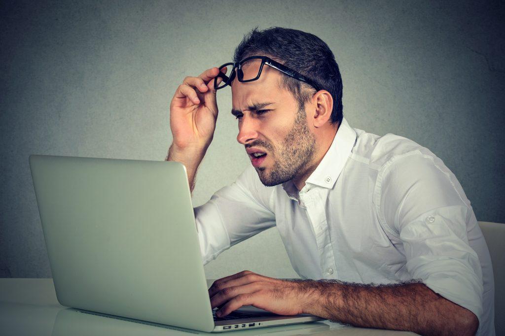 パソコンを見て困っている男性