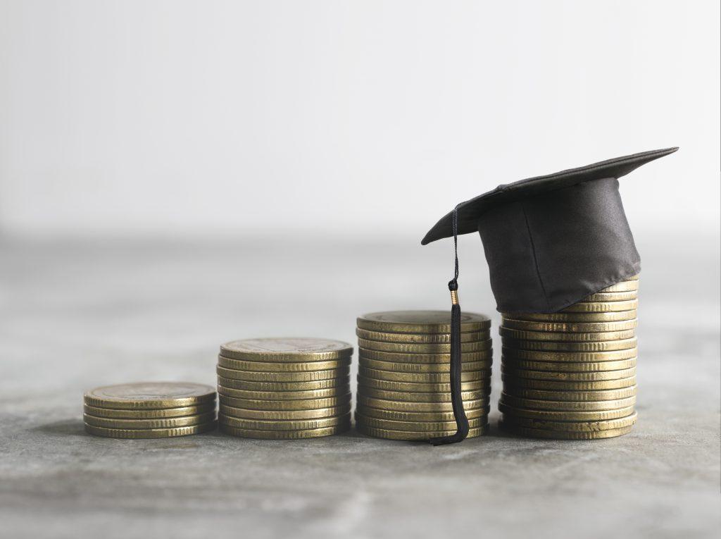 積まれたお金と卒業帽子