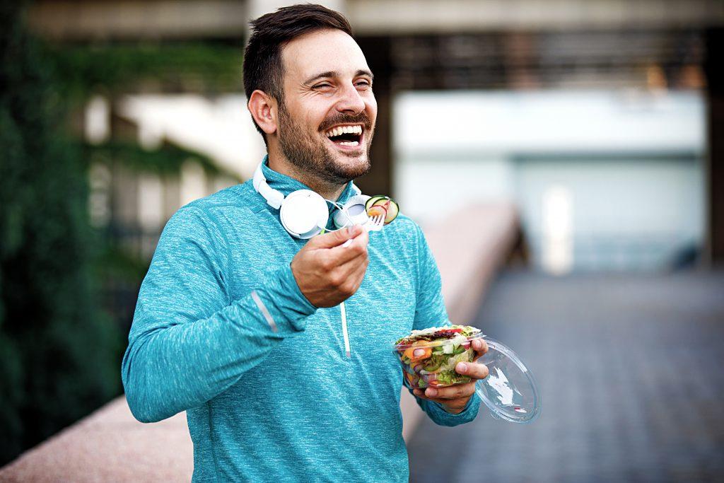 笑顔の男性がサラダを食べている