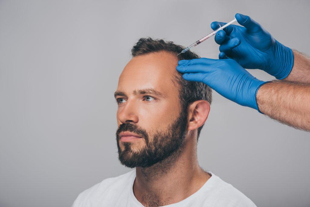 生え際に注射をされている男性