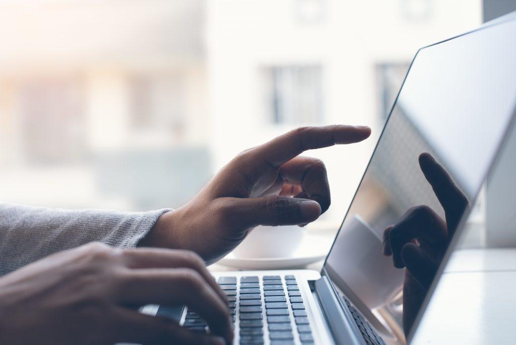 男性がパソコンの画面に指をさしている