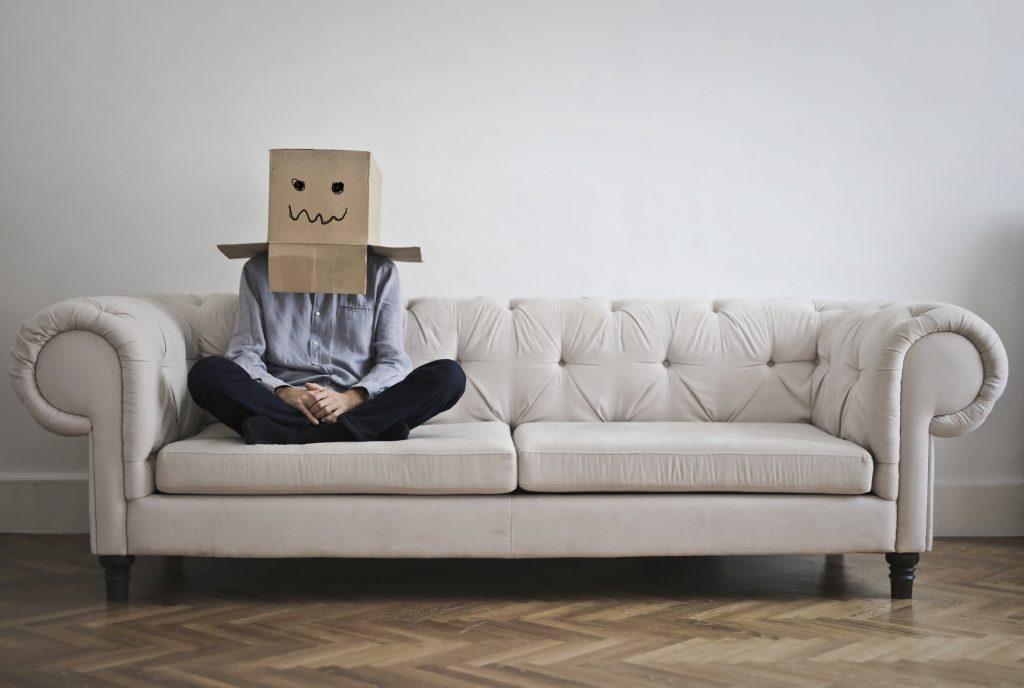 頭に段ボールをかぶってソファーに座る男性