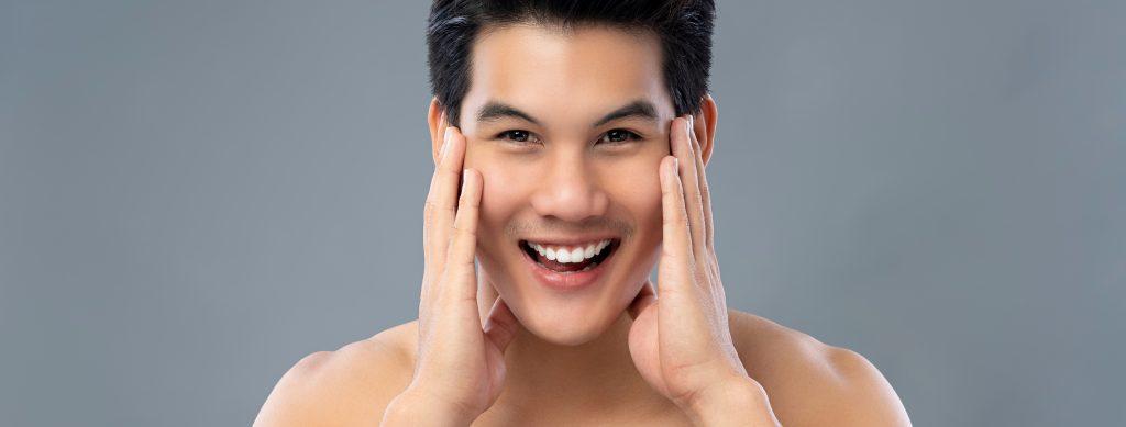 笑顔で顔を触る男性