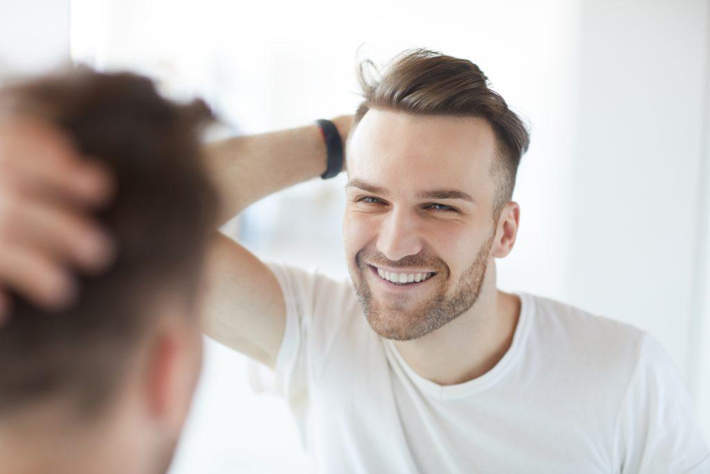 鏡をみて微笑んでいる男性