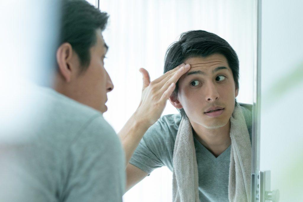 鏡を見て手入れをする男性