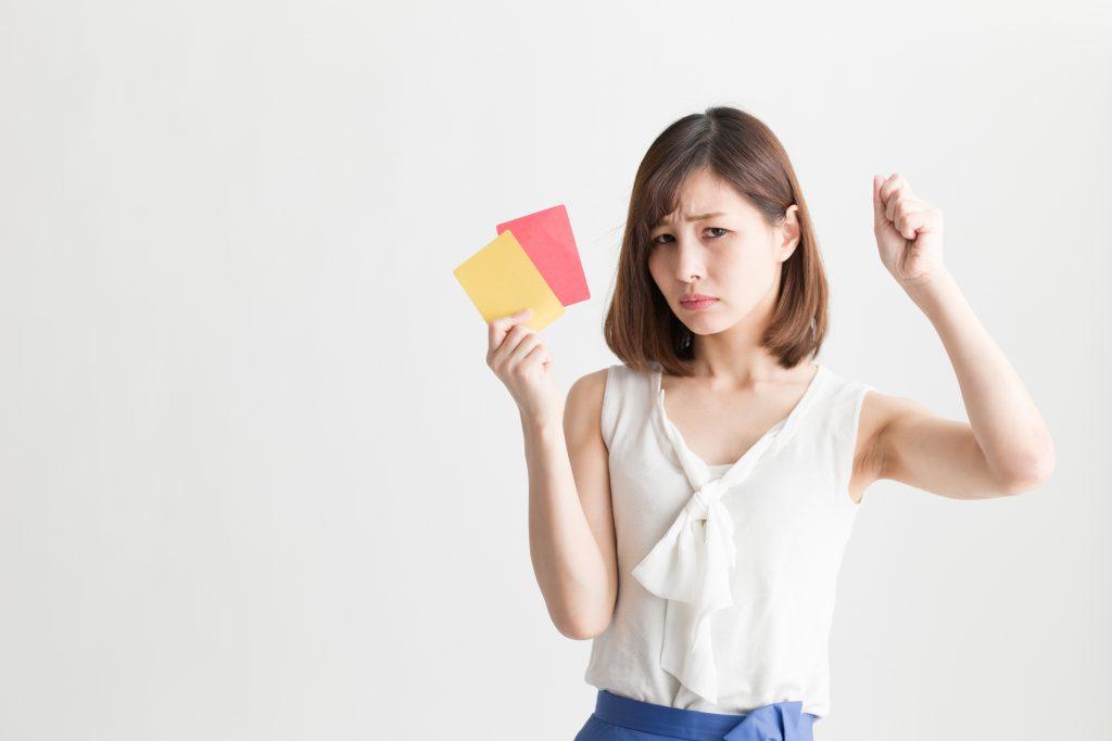 黄色と赤いカードを持っていやがっている女性