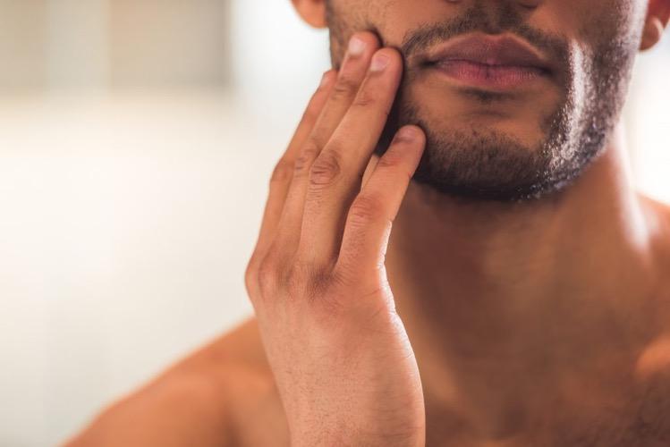 あごひげを触る男性